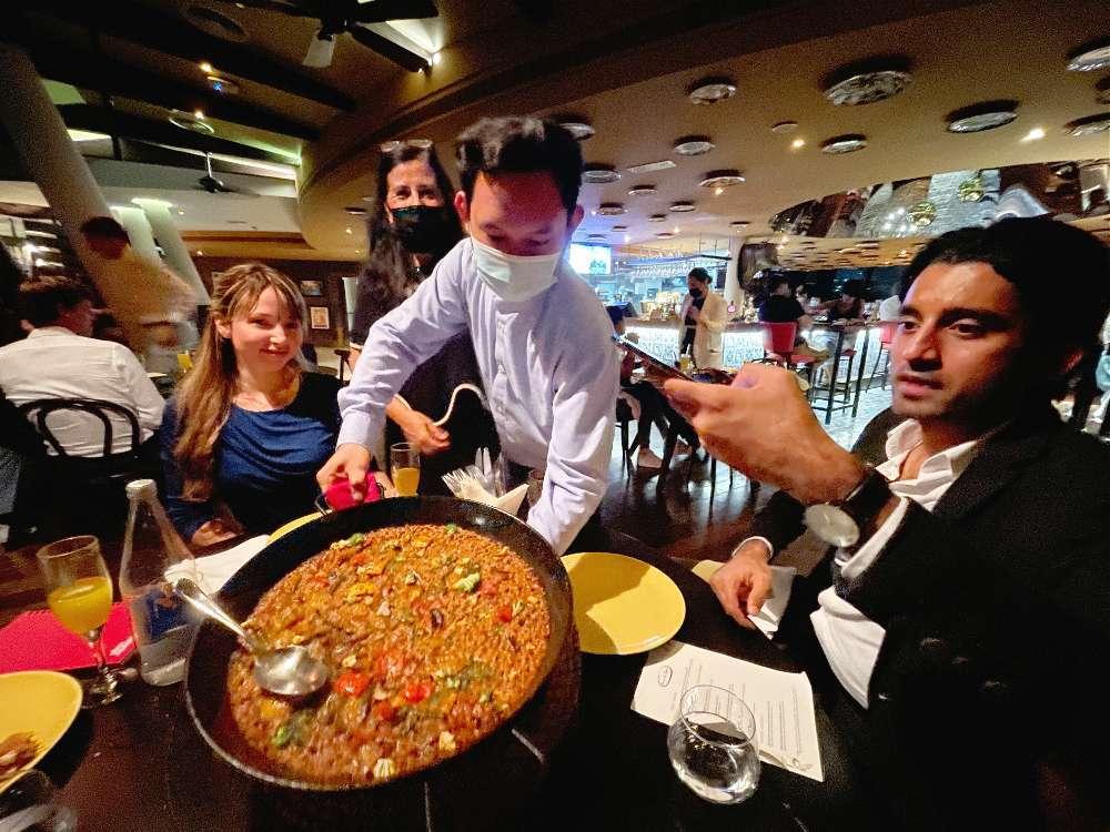 De izquierda a derecha, Beatriz Lastre, Amelia Cruzado y Naved Ullah reciben en su mesa una espectacular paella. (EL CORREO)