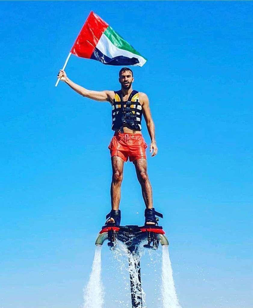 Turista levanta la bandera de Emiratos Árabes elevado sobre el mar por medio de propulsores acuáticos. (WAM)