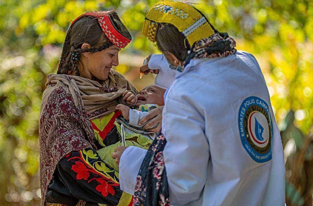 Un bebé en brazos de su madre llora mientras recibe la dosis contra la polio en Pakistán. (WAM)