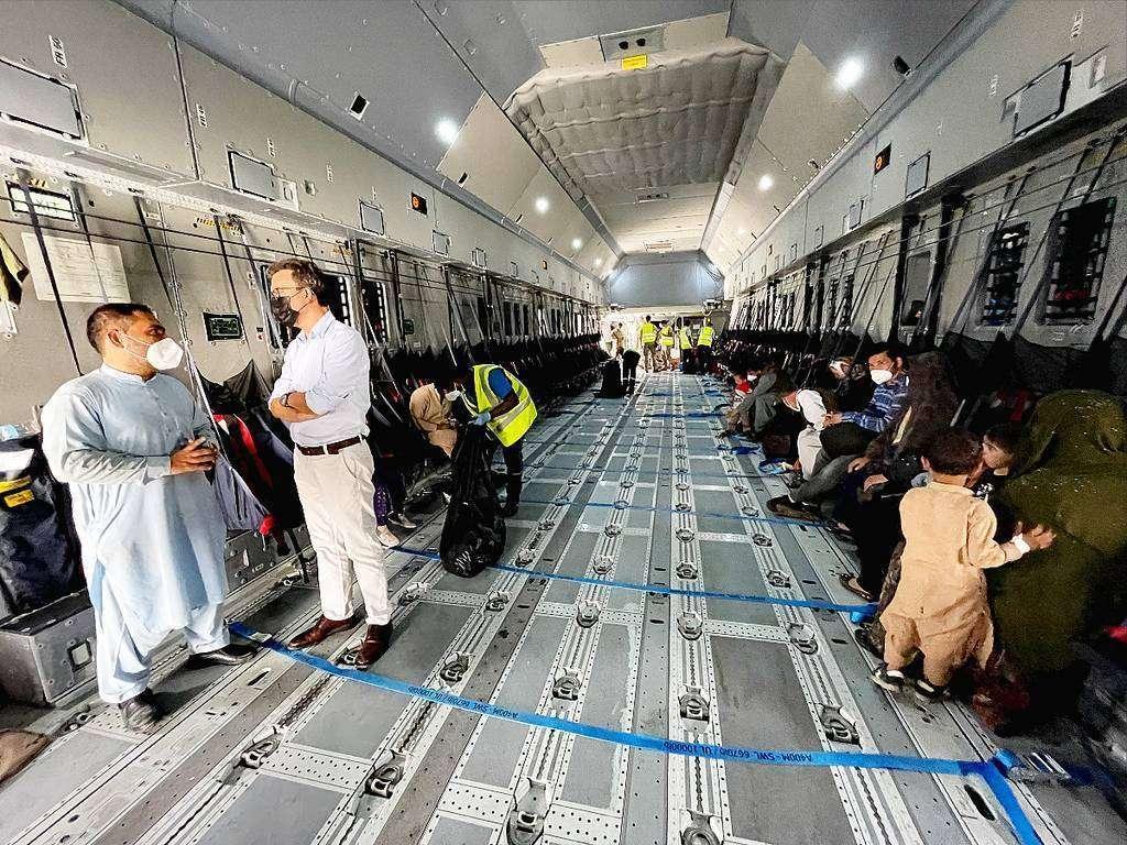 El embajador de España en Emiratos Árabes -derecha- conversa con el afgano Nasir Khan en el avión militar español en que fue evacuado de Kabul a Dubai. (EL CORREO)