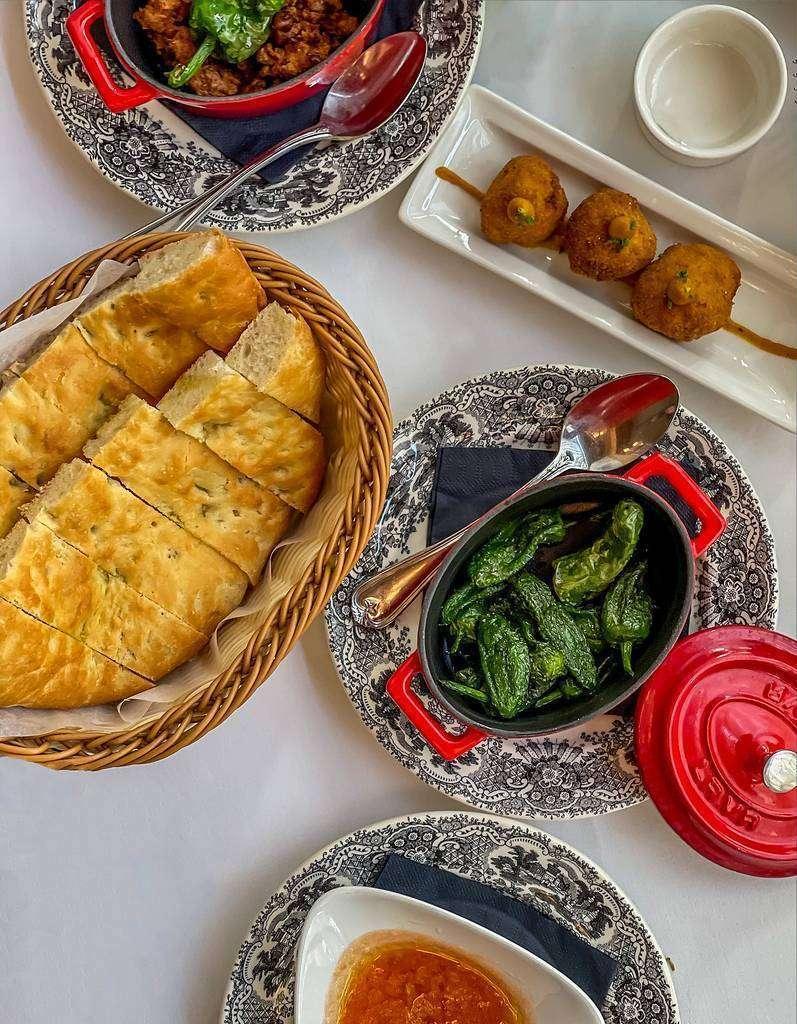 Distintas propuestas sobre la mesa de Asador de Aranda en Dubai, entre ellas la exquisita torta de Aranda. (EL CORREO)