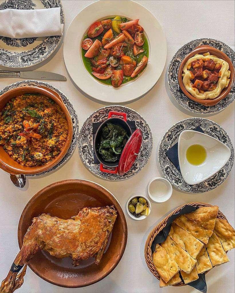 Distintos platos en Asador de Aranda en Dubai, entre los cuales no falta la torta de Aranda ni el arroz caldoso. (Cedida)